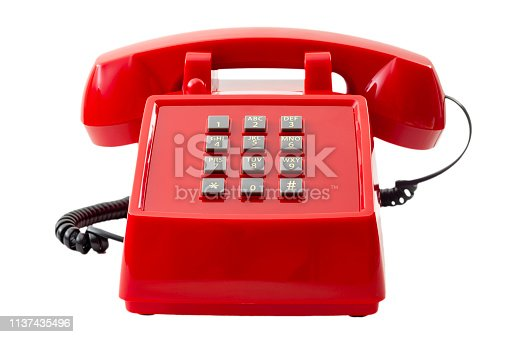 Vintage telecommunication technology and retro household items concept with a red push button telephone isolated on white background with a clipping path cut out