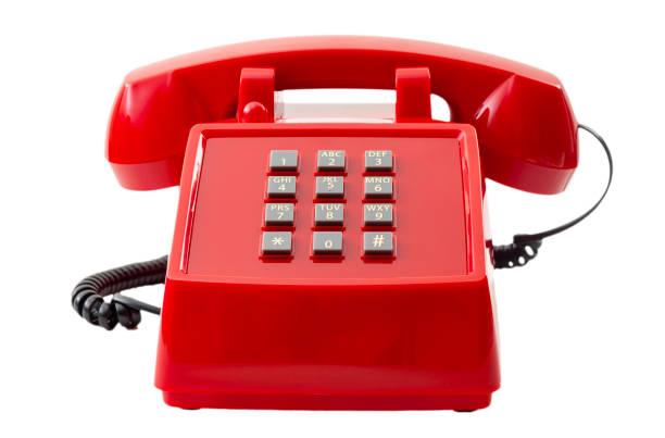 La tecnología de telecomunicaciones vintage y el concepto de artículos domésticos retro con un teléfono pulsador rojo aislado sobre fondo blanco con un recorte de la trayectoria del clip - foto de stock