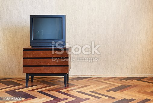 Vintage Television on wooden antique closet, old design in a home.The interior in the style of the 90s.