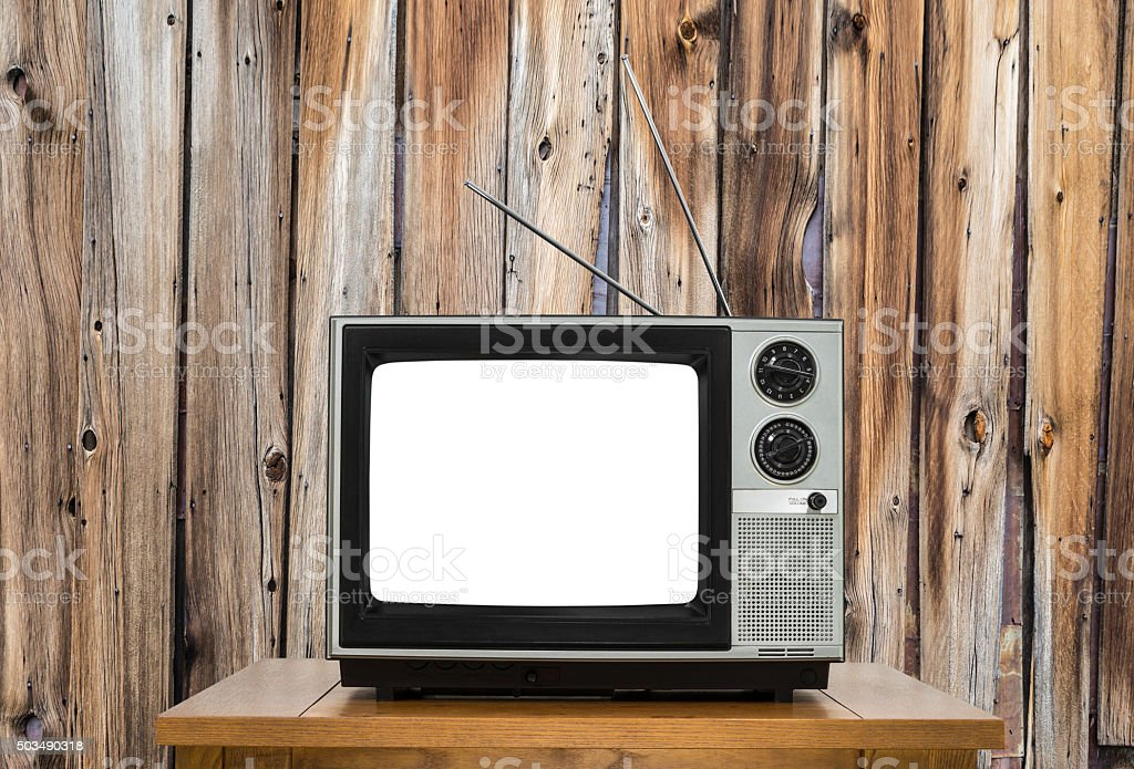 Vintage television with rustic wood wall and cut out screen.