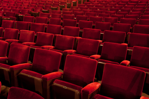 Vintage red seats inside an old performance hall.