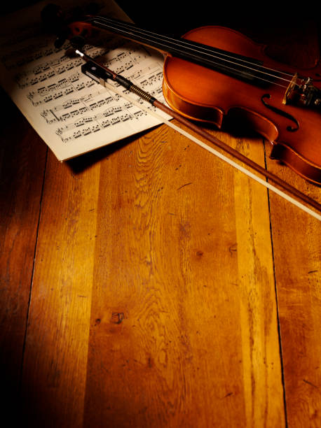 Vintage Themed Violin and Sheet Music Wooden violin and bow on sheet music, with copy space on a old wooden oak table. string instrument stock pictures, royalty-free photos & images