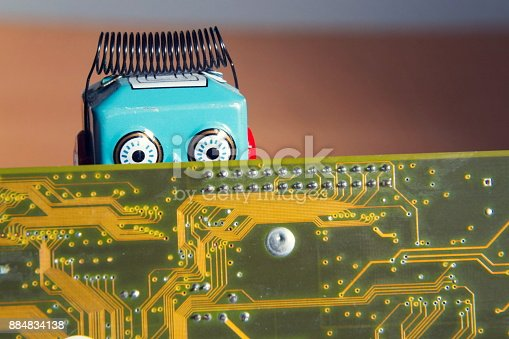 istock Vintage tin toy robot behind computer board, artificial intelligence concept 884834138