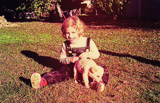 Vintage toned image of a girl sitting outdoors and playing with a puppy.