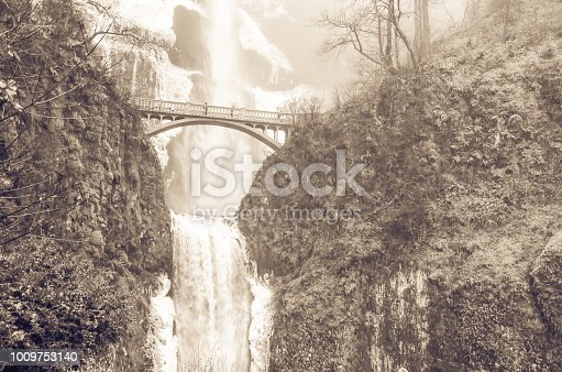 Vintage tone beautiful pedestrian stone bridge and knee-wobbling vantage point over the second tier 69-foot drop of Multnomah Falls lower in winter time. Natural and seasonal waterfall background