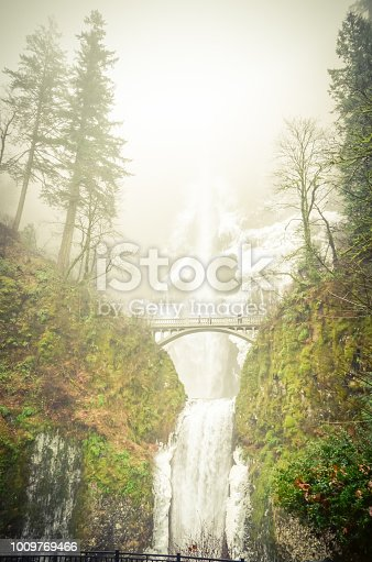 Vintage tone icy Multnomah Falls in winter time. It is a waterfall on the Oregon side of the Columbia River Gorge, along the Historic Columbia River Highway. Natural and seasonal waterfall background