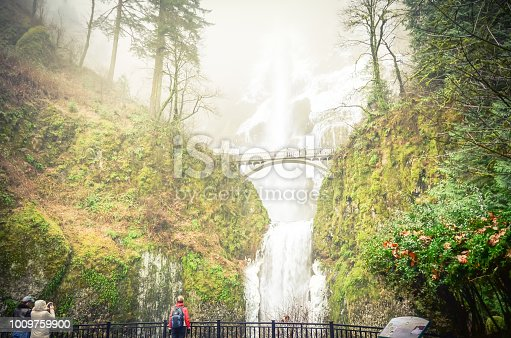 Vintage tone crowded of visitor at the main lookout of the base of Multnomah Falls in winter time. A waterfall on the Oregon side of the Columbia River Gorge, along the Historic Columbia River Highway