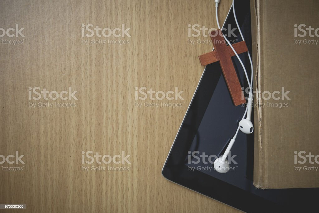 vintage tone. mock up table with cross and ear pod stock photo