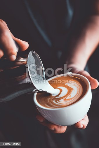 istock vintage tone of some people pour milk to making latte art coffee at cafe or coffe shop 1135265951