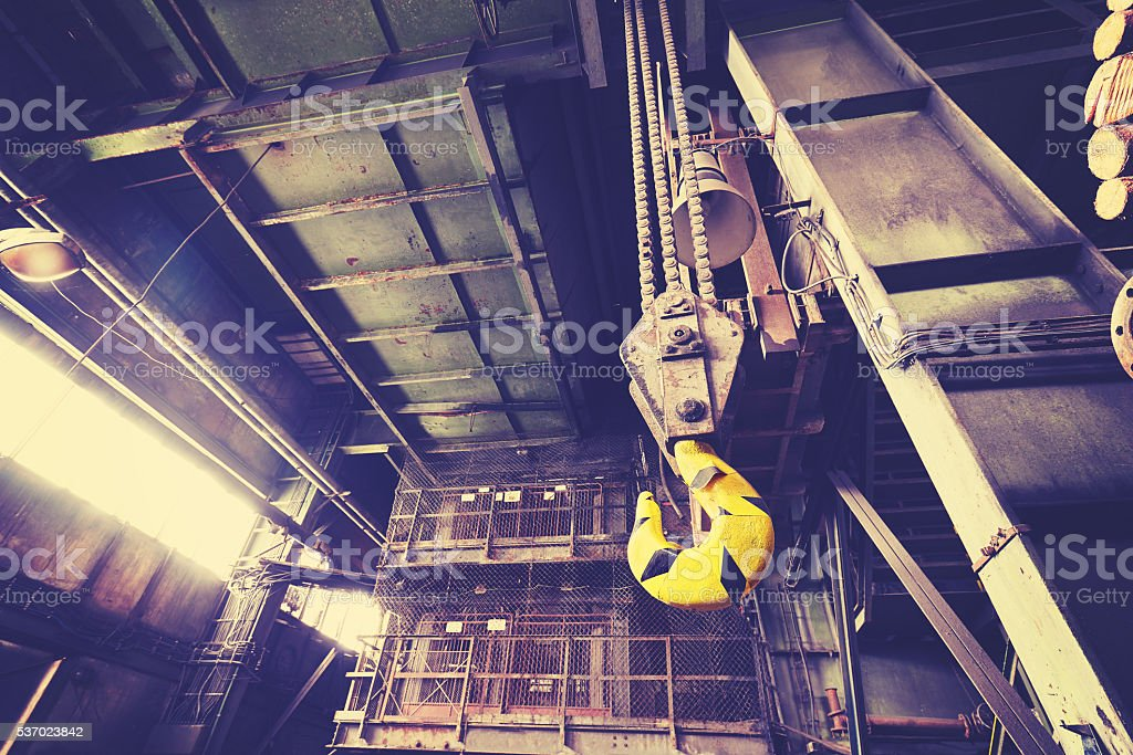 Vintage toned crane hook in abandoned coal mine. stock photo