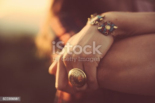 Close-up image of a woman's hand, wearing a fashionable vintage oriental ring and a bracelet. Shot in pastel, cross processed tones of film emulation, with Canon full frame camera EOS 5d mark 2 with large aperture zoom lens Sigma 28-75 at f2,8 with only natural light.