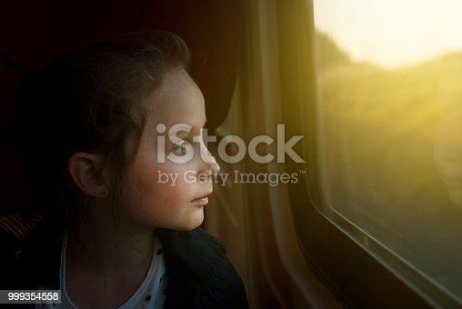 Vintage toned mage of Little Girl looking through window. She travels on a railway train.