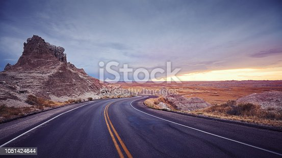 Vintage toned panoramic picture of a scenic road at sunset, USA.