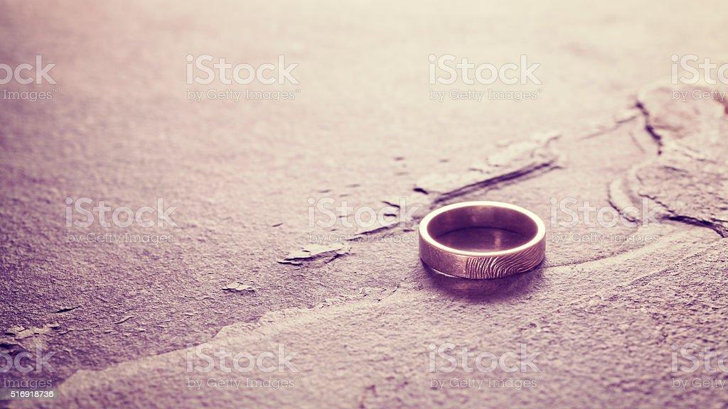 Vintage toned single wedding ring on stone background. stock photo
