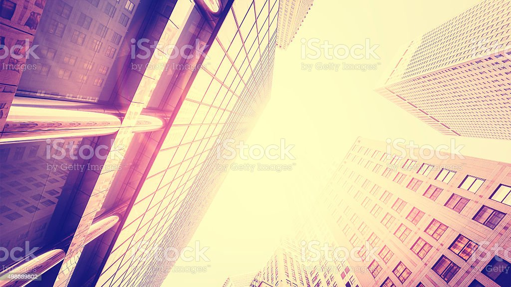 vintage toned skyscrapers against sun lens flare effect stock photo