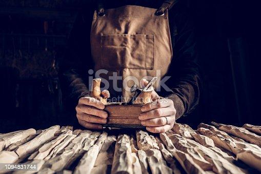 detail of hands holding vintage hand planer