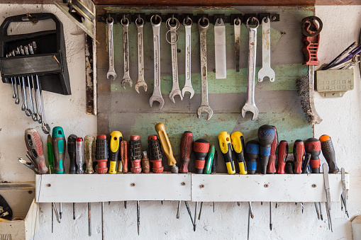 Vintage Tools Hanging On A Wall In A Garage Or Workshop