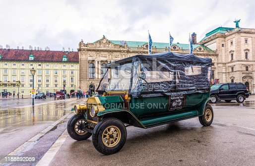 Vienna, Austria - July 13, 2019: vintage pleasure car for tourists on a historic street in Vienna, Austria. Summer rainy day and surroundings of the royal residence of the Habsburgs, a tour of Vienna's tourist attractions