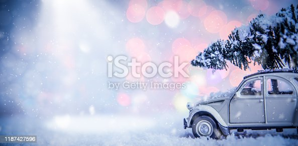 Vintage car with fir tree in a snowy winter day