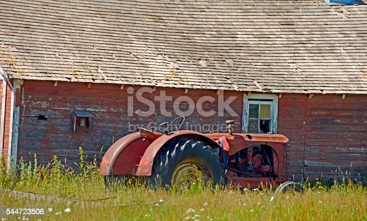 Vintage Tractor next to olf farm building