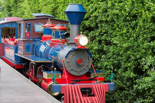 Hong Kong, Сhina - September 2, 2013: Tourists take the vintage train at Hong Kong Disneyland to circle around the theme park.
