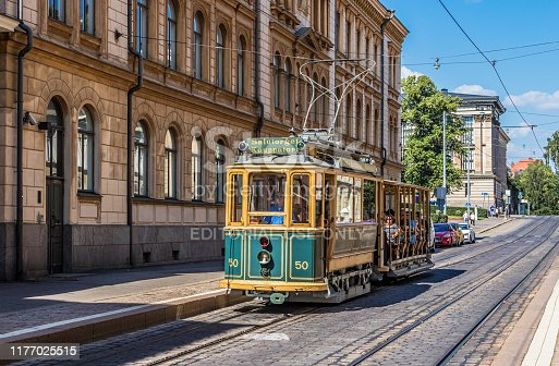 Helsinki, Finland; July 27, 2019: Vintage tram tour of Helsinki running down cobblestone street, passing heritage buildings in background. Destination sign says
