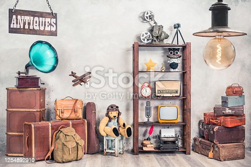 istock Vintage travel suitcases, backpack, old gramophone, TV, radio, mic, projector, clock, typewriter, quill, books, camera, Teddy Bear, toy plane, signboard, mask. Antiques collectibles. Retro style photo 1254892910