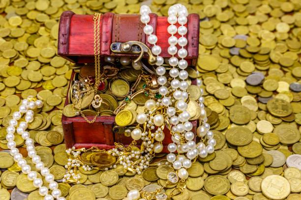 vintage schatztruhe voller goldmünzen und schmuck auf einem hintergrund von goldenen münzen - goldgefüllte kette stock-fotos und bilder