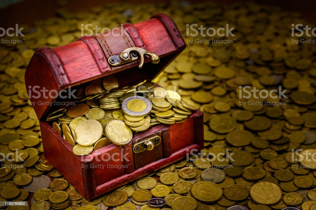 Vintage treasure chest full of gold coins on a background of golden...