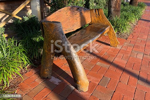 a beautiful old vintage tree stump carved wood garden park bench on a cobblestone path at sunrise with shadows
