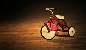 cast iron vintage tricycle  standing on a wooden floor