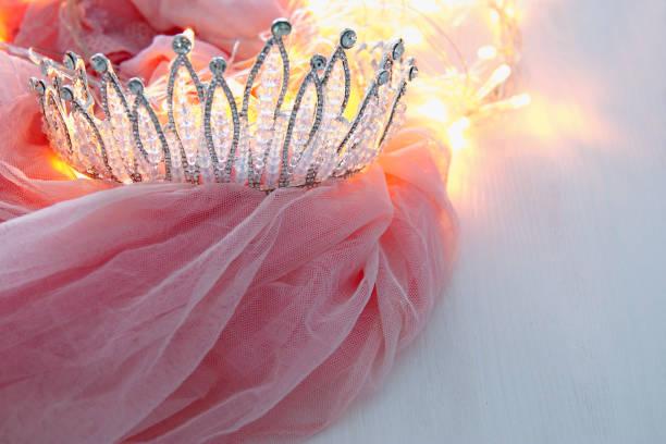vintage tüll rosa chiffon kleid und diamant tiara auf weißer holztisch. hochzeit und party-konzept des mädchens - prinzessin tiara stock-fotos und bilder