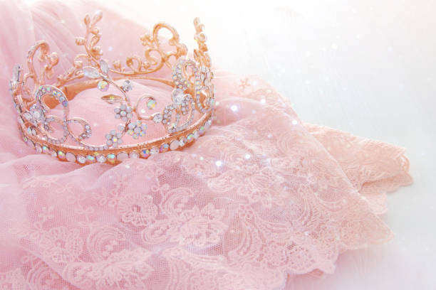 vintage tulle pink chiffon dress and diamond tiara on wooden white table. wedding and girl's party concept - principessa foto e immagini stock
