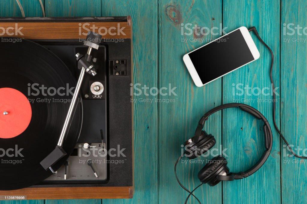 Vintage turntable, smartphone and headphones stock photo