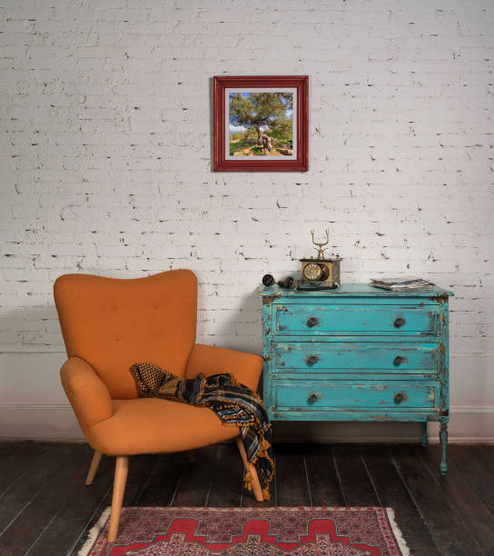 Vintage turquoise cabinet with orange stylish armchair in room interior stock photo