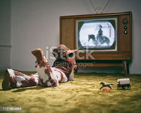 A period correct 1960's television displaying a cowboy scene on the screen (not simulated) with a little boy dressed as a cowboy watching the screen. Image toned to match the era.