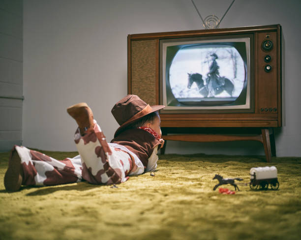 Vintage TV and Little Boy Cowboy A period correct 1960's television displaying a cowboy scene on the screen (not simulated) with a little boy dressed as a cowboy watching the screen. Image toned to match the era. 20th century style stock pictures, royalty-free photos & images
