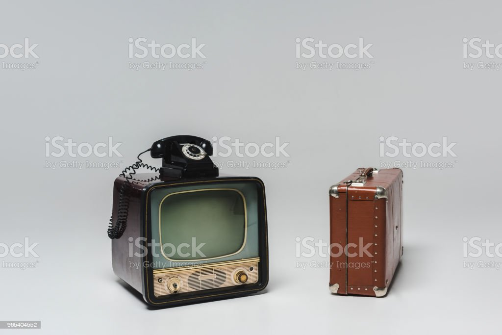 vintage tv with rotary phone and suitcase on grey zbiór zdjęć royalty-free