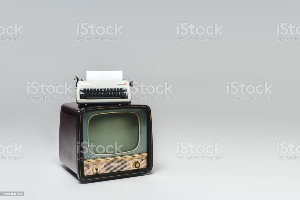 vintage tv with typewriter on top on grey surface royalty-free stock photo
