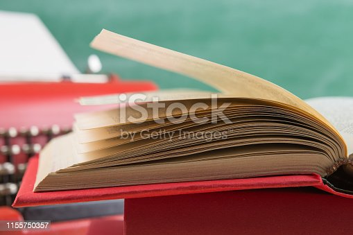 istock vintage typewriter and book close up on the table - writing or journalism concept 1155750357