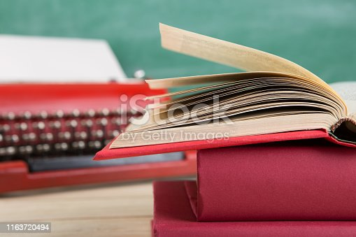 istock vintage typewriter and book close up on the table - writing or journalism concept 1163720494