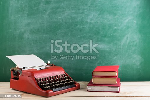 istock vintage typewriter and books on the table with blank paper on wooden desk 1149567945
