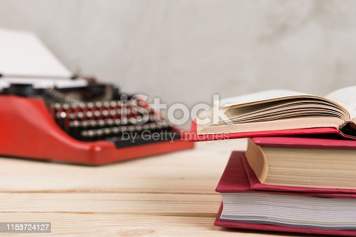 istock vintage typewriter and books on the table with blank paper on wooden desk 1153724127
