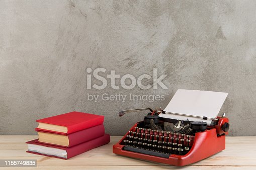 istock vintage typewriter and books on the table with blank paper on wooden desk 1155749835