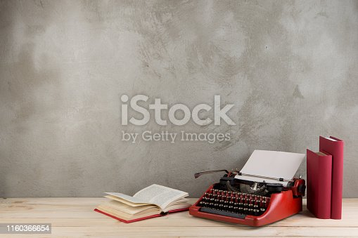 istock vintage typewriter and books on the table with blank paper on wooden desk 1160366654
