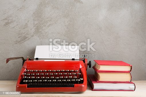 istock vintage typewriter and books on the table with blank paper on wooden desk 1160366660
