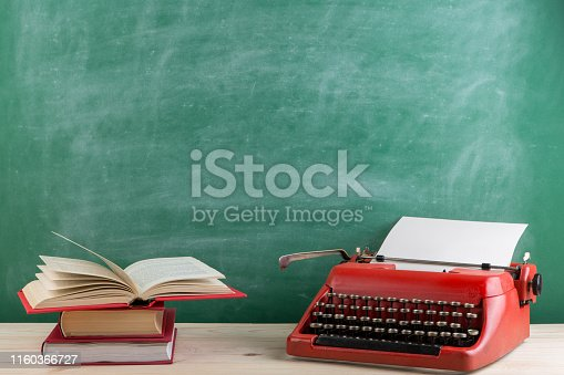 istock vintage typewriter and books on the table with blank paper on wooden desk 1160366727