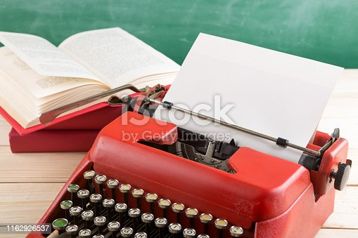 istock vintage typewriter and books on the table with blank paper on wooden desk 1162926537