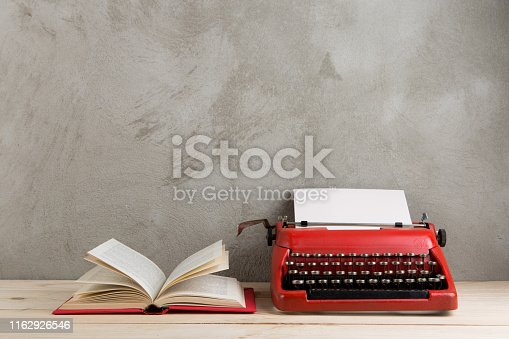 istock vintage typewriter and books on the table with blank paper on wooden desk 1162926546