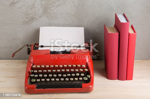 istock vintage typewriter and books on the table with blank paper on wooden desk 1163720478